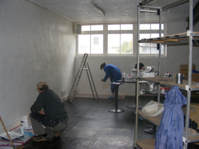 volunteers painting the interior of the empty shop in 2013