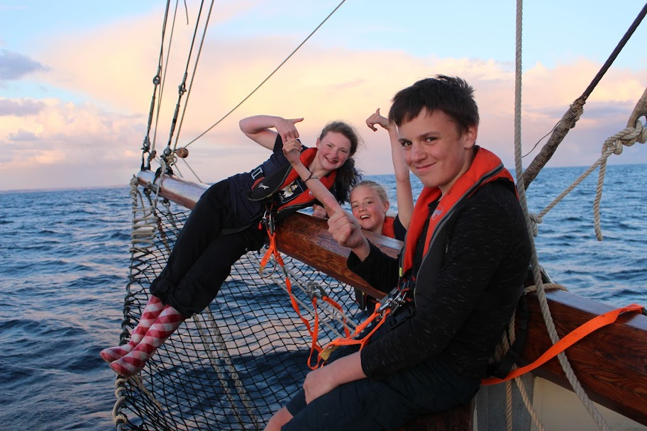 3 kids on bow of yacht