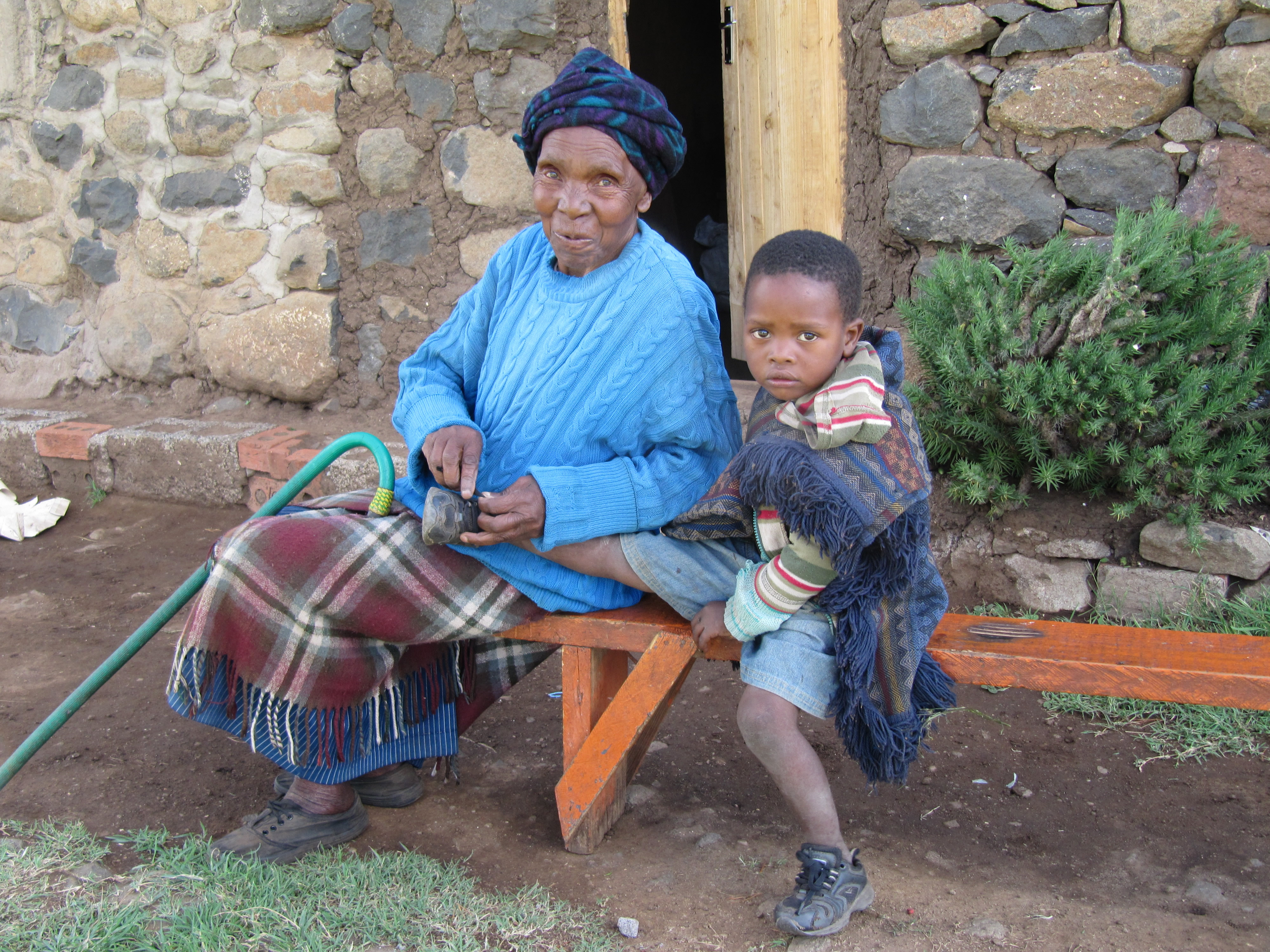 Grandma and grandson tying shoelaces in Lesotho
