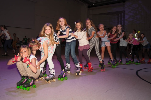 Girls doing conga line at roller disco in Paisley